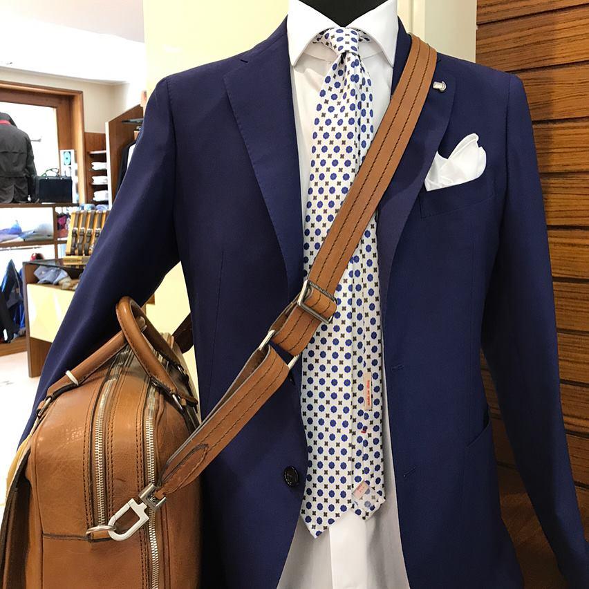 un manichino con una camicia, una giacca blu e una borsa di pelle tracollo