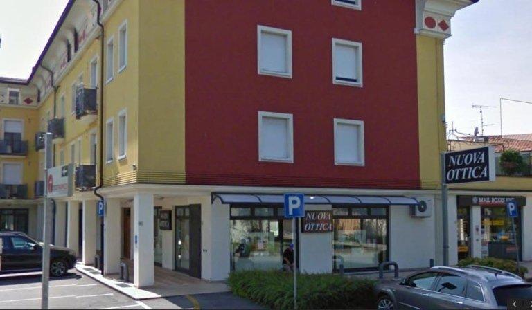 un edificio giallo e rosso e un negozio di ottica sotto