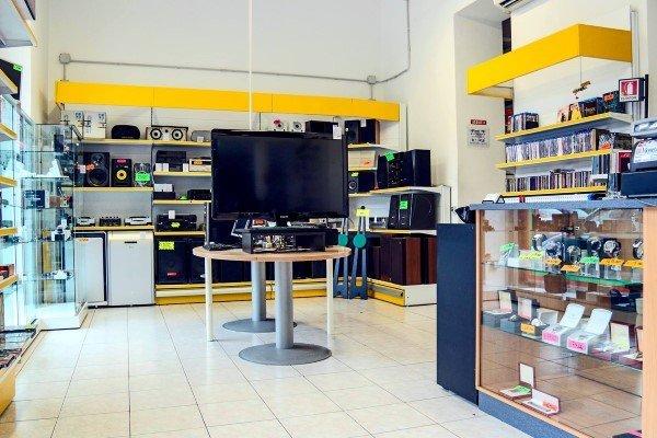 interno negozio con tv al centro e apparecchi audiovisuali sugli scaffali dietro