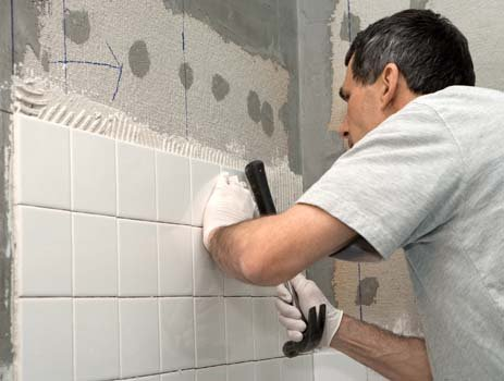 Bathroom wall tiles being installed by expert