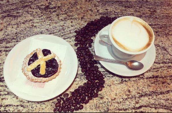tazza di cappuccino con un dolcetto e chicchi di caffè