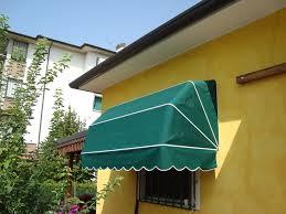 muro giallo acceso con tenda da sole verde