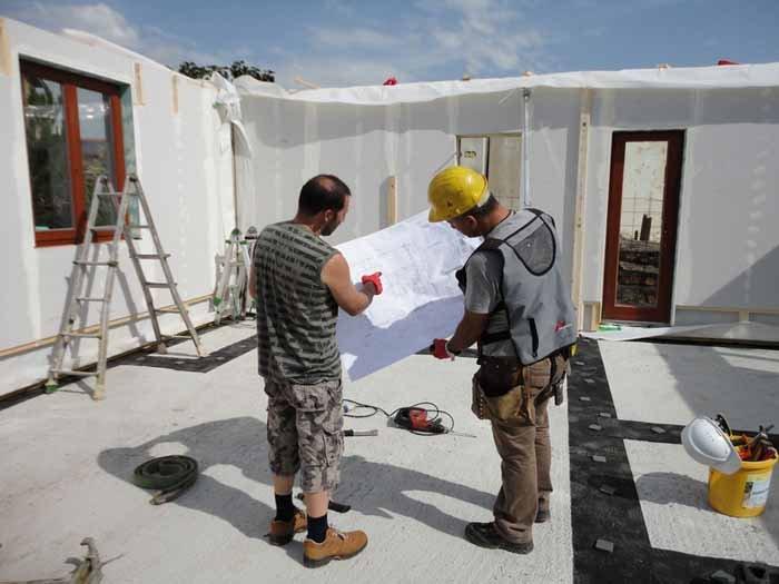 gli ingegneri del cantiere con disegno di casa