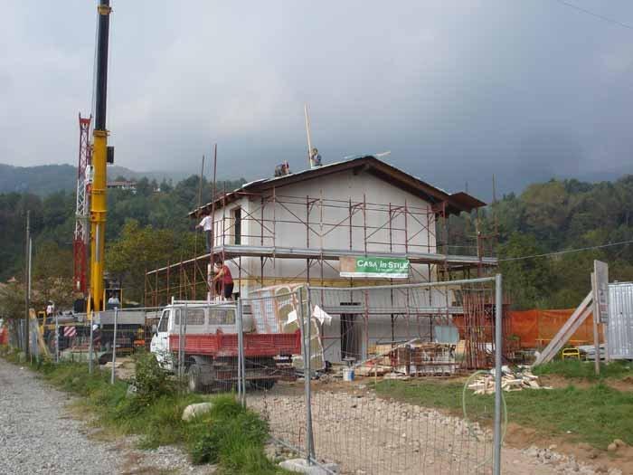 vista di una casa in costruzione con gru lato di strada