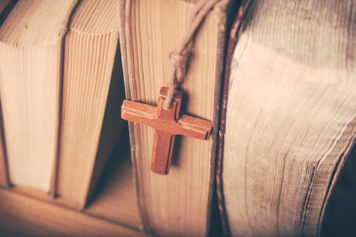 Piccola croce di legno appeso su un vecchio libro