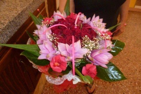 Composizione di fiori vari con nucleo di rose rosse