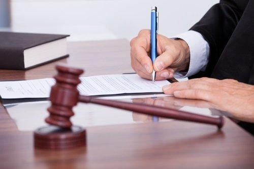 avvocato mentre firma un foglio