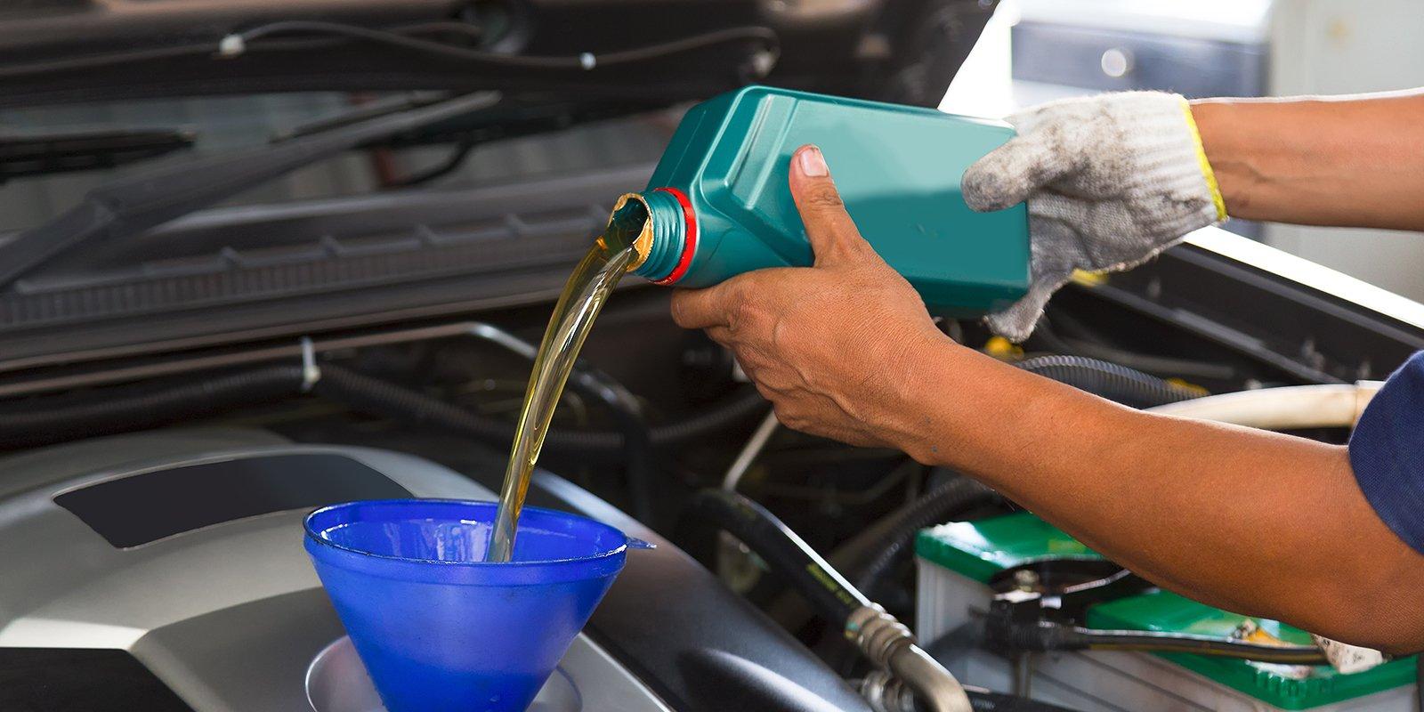 due mani che versano dell'olio in una macchina