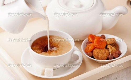 una brocca che versa del latte in una tazza di caffe' e accanto della frutto secca