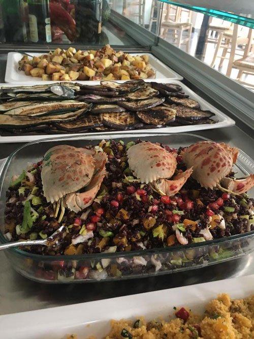 una pirofila con dell'insalata di mare con dei granchi  e del melograno