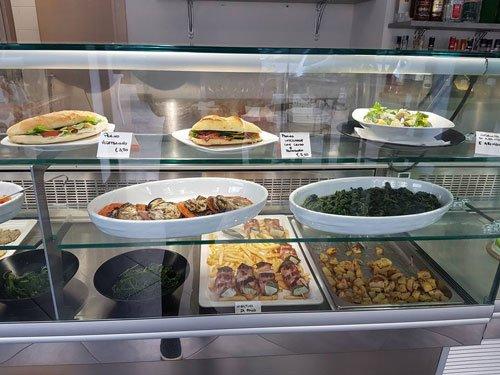 dei piatti pronti in esposizione in una vetrina di un buffet