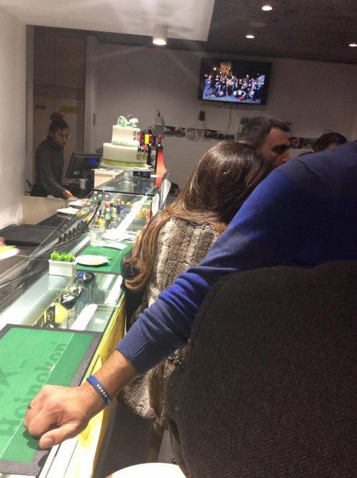 delle persone in piedi nel ristorante e una tv accesa
