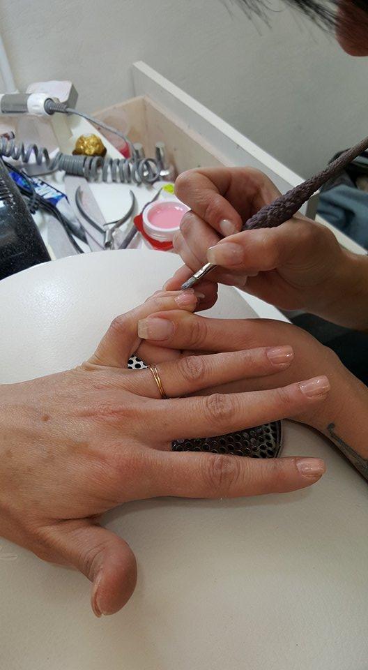 estetista durante l'applicazione di smalto per unghie