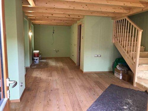 Interno di appartamento con scala, pavimento e travi in legno