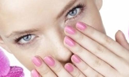 una donna con smalto rosa su unghie davanti al viso
