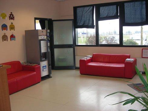 sala di attesa con due divani rossi