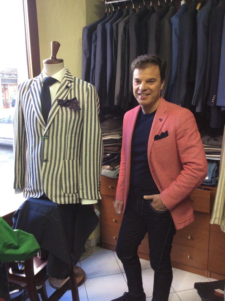 un uomo con una giacca di color rosa e dei jeans di color nero
