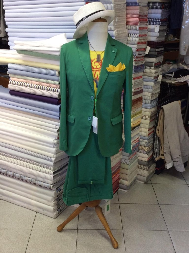 un manichino con una maglia di color giallo e una giacca e dei pantaloni di color verde