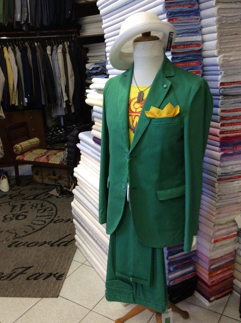 un manichino con una maglia di color giallo e una giacca e dei pantaloni di color verde e un cappello di color bianco