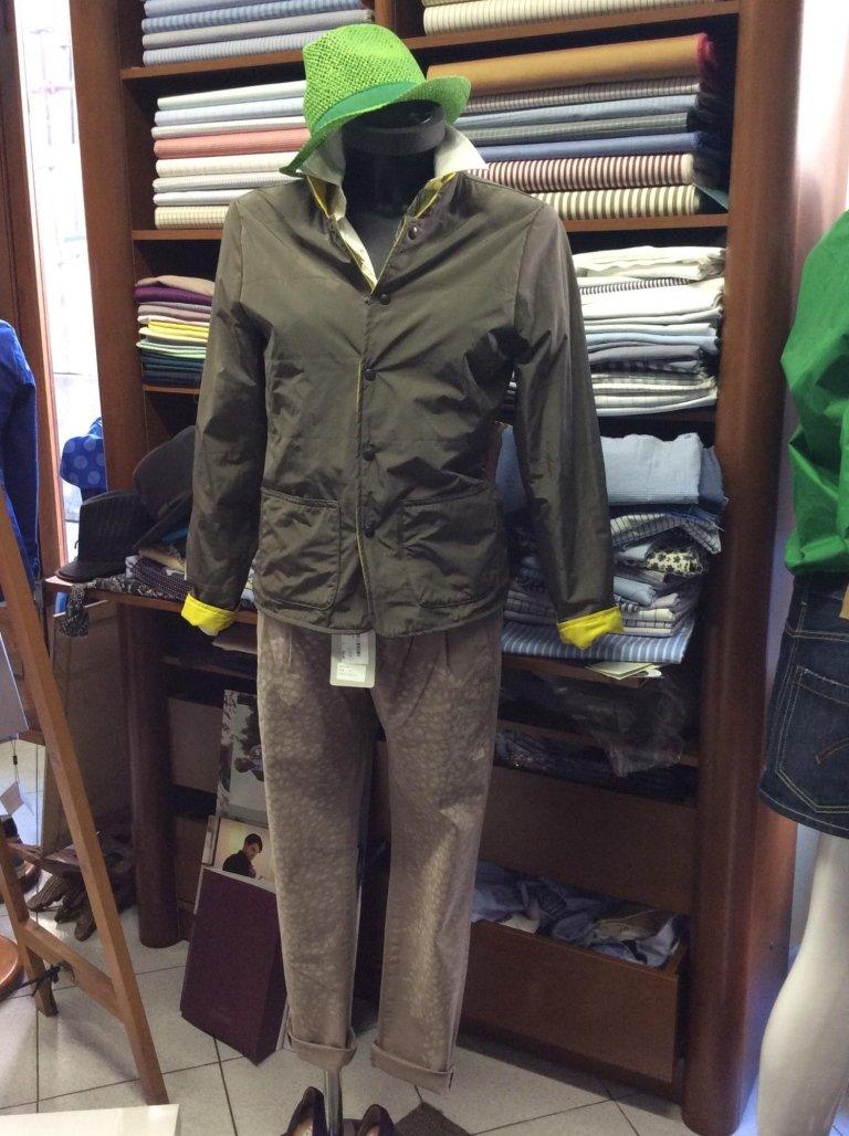 un manichino con dei pantaloni di color marrone e un impermeabile di color verde