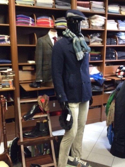 un manichino con dei pantaloni di color beige e una giacca e cappello di color blu