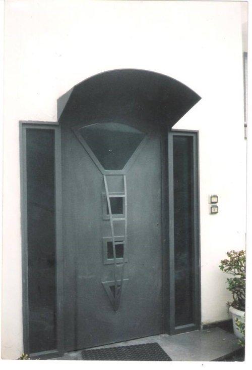 una porta d' ingresso di color nero e sopra una pensilina
