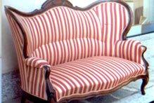 un divano in legno con una stoffa con delle righe di color rosso e bianco