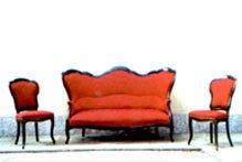 un divano e due poltrone in legno di color rosso