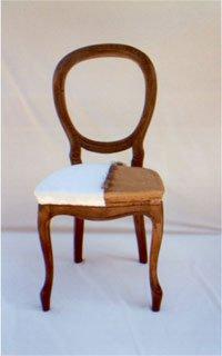 una sedia in legno con cuscino di color bianco