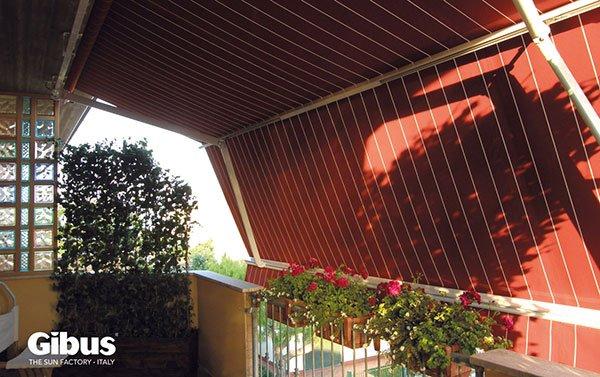 una terrazza con un tenda da sole di color rosso