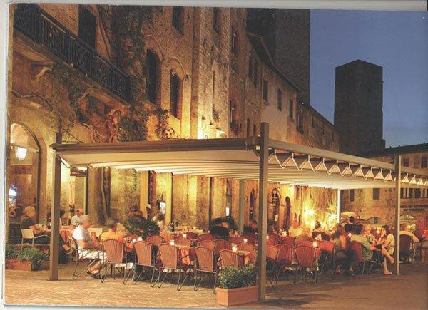 dei tavoli con le sedie sotto una tenda davanti a un ristorante