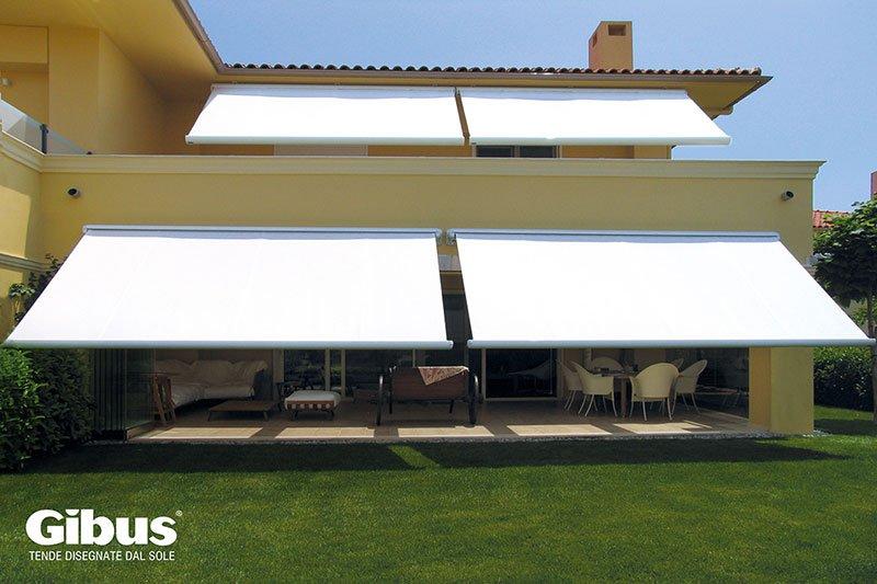 una villa con delle tende da sole di color bianco
