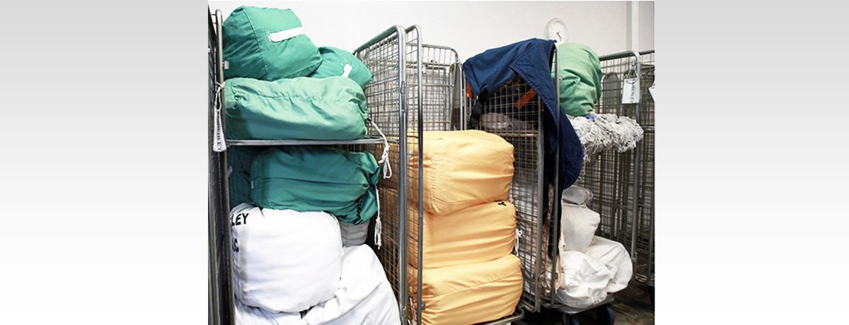 new look drycleaners and laundry service pile of laundry stacked on trolley