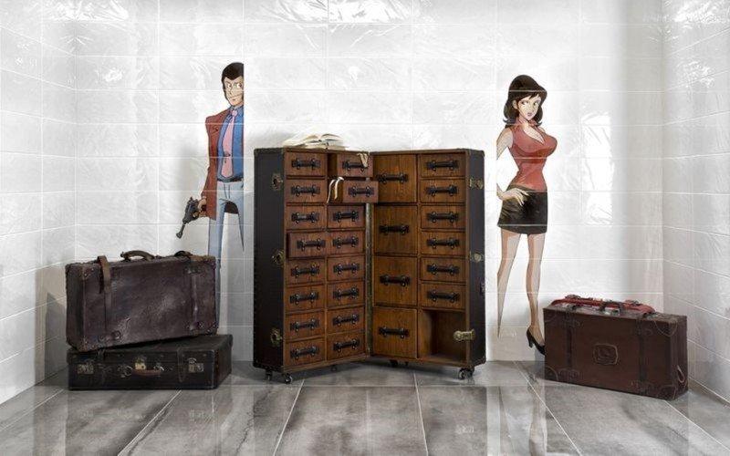 Personaggi di fumetti spiano dalla parete su entrambi i lati di un baul antico di viaggio