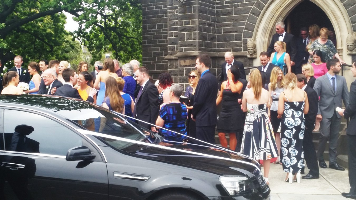 happy crowd in front of chauffeured wedding cars melbourne