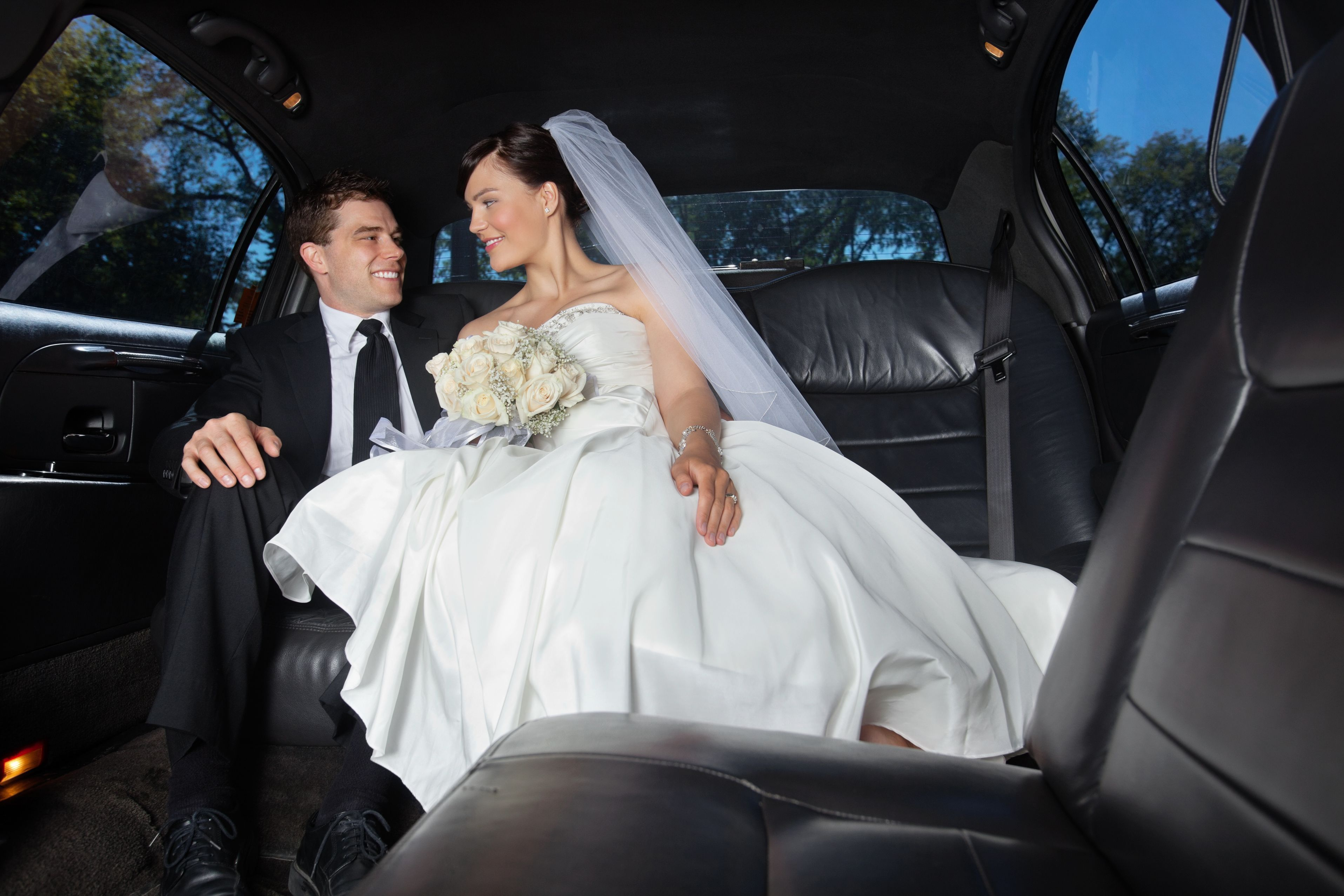 Newlywed bride and groom in chauffeur driven cars