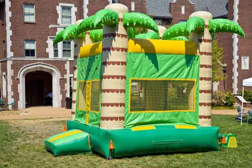 A colorful big bounc house for kids to jump on in the outdoors