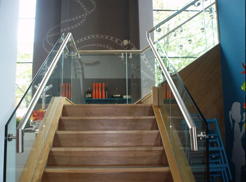 Wooden stairs with a glass balustrade in a restaurant