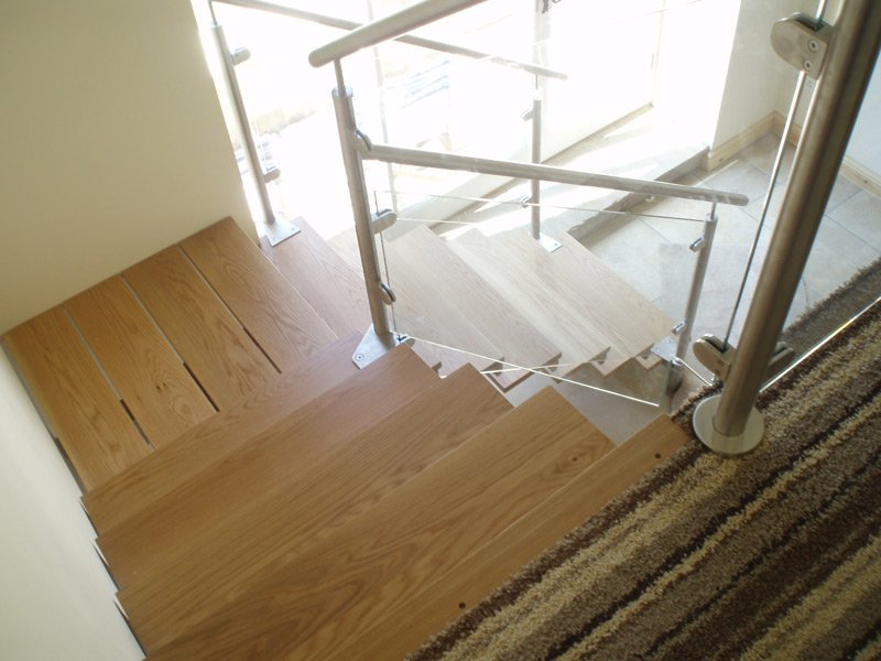 Looking down a wooden staircase with glass balustrades and metal handrails