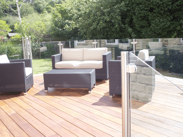 Cane furniture on decking with glass balustrades
