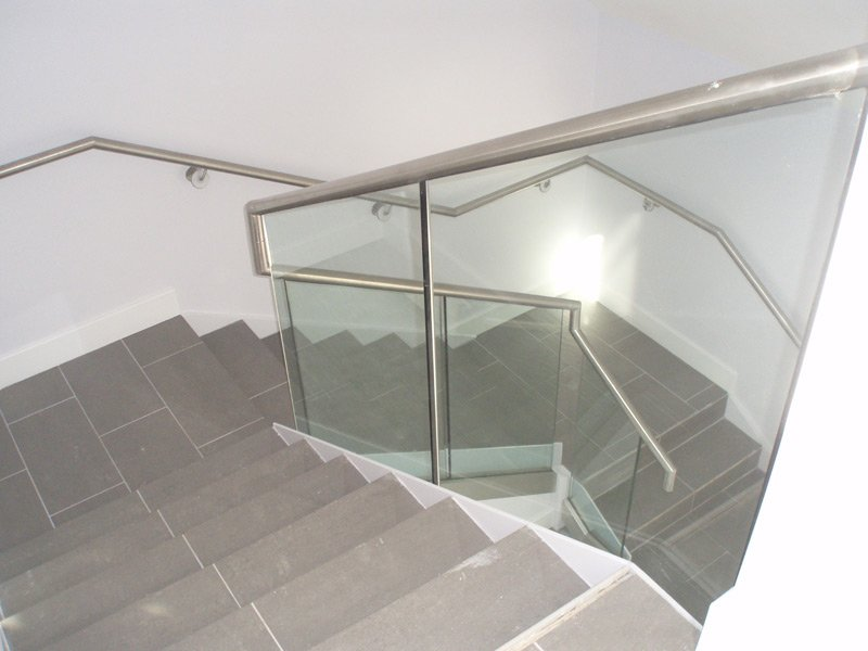 Looking down a staircase with glass balustrades and metal handrails
