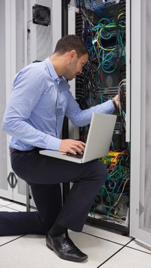 An IT technician working on data cabling
