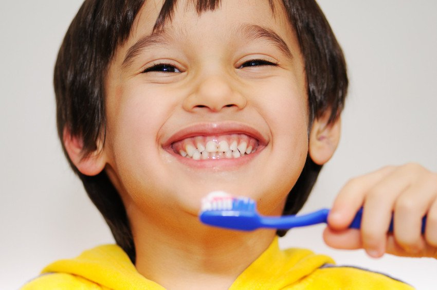 A young boy brushes his teeth and shows his smile