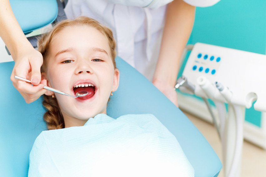 A young girl receives dental treatment