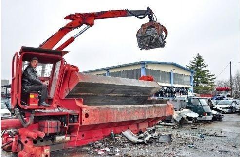 vista laterale di un gru con operaio mentre lavora per demolizione auto