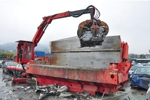 vista frontale di un gru con operaio mentre lavora per demolizione auto