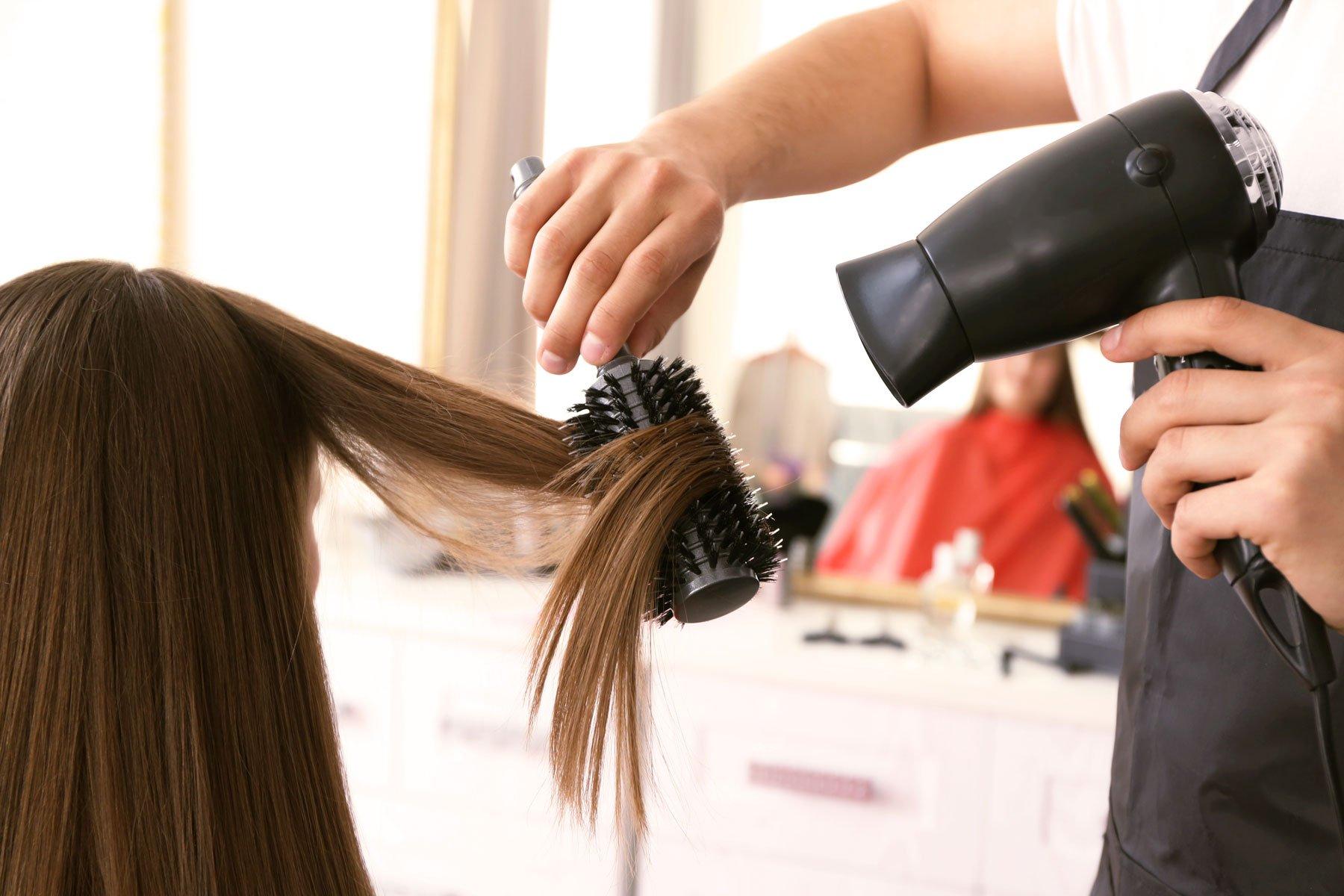Una parrucchiara arriccia i capelli di una donna