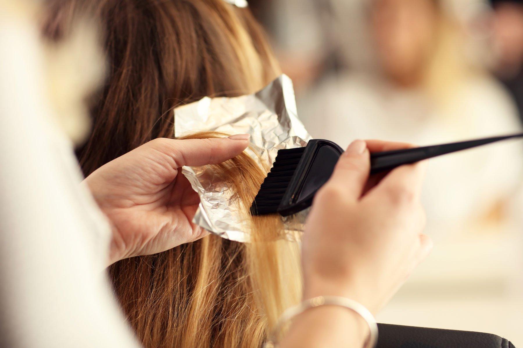 Una parrucchiere mette il colore su una ciocca di capelli