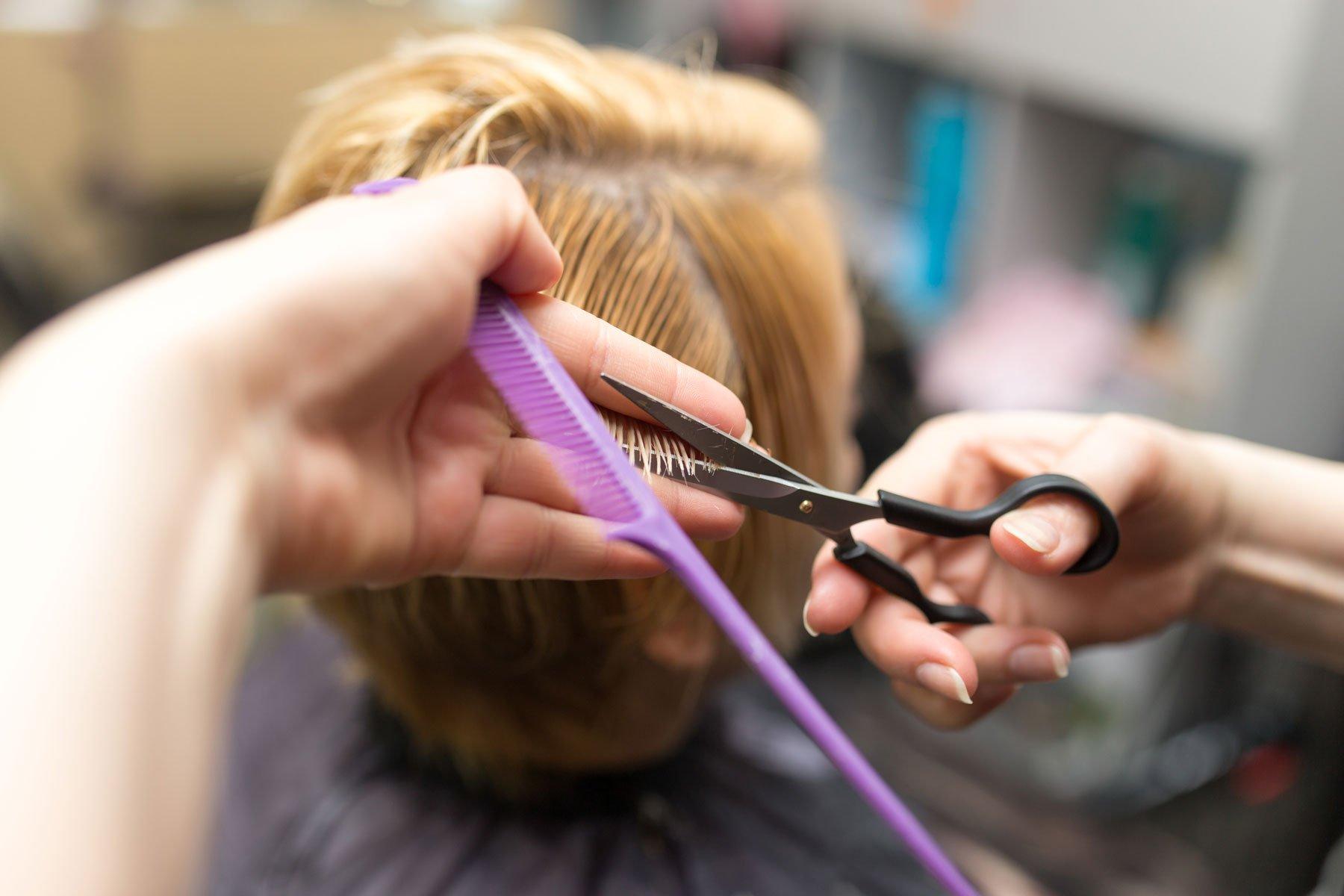 Una parrucchiera taglia dei capelli