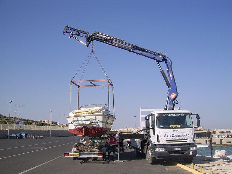 un camion con un braccio meccanico che solleva una barca da un carrello